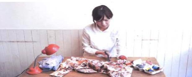 Japanese woman turning a used kimono into new household articles, following a cultural tradition called mottainai.