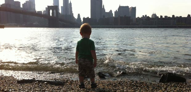 Childfree Green GINK Child overlooks the East River from Brooklyn towards Manhattan