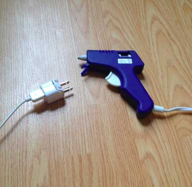 Image of a glue gun and a phone charger