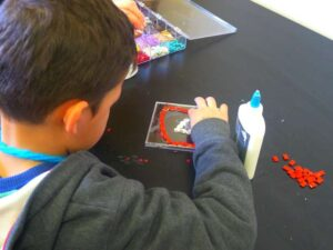 A student crafting a CD case mosaic
