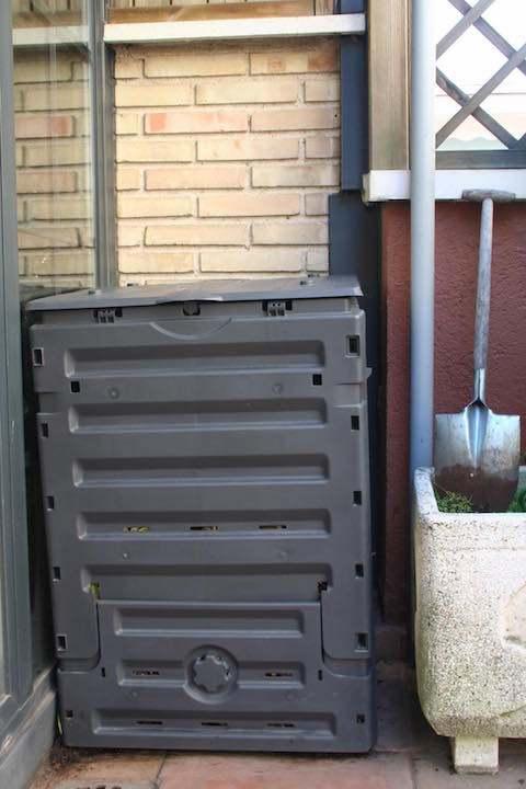 Plastic compost bin in corner of terrace