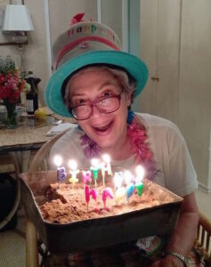 Jacquie Ottman about to blow out the candles on her Gur birthday cake made for her Leftovers Pooling Birthday Party.