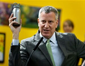 NYC Mayor Bill De Blasio holds up a reusable water bottle as an example of a change he made for the environment.