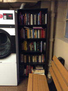Little free library on repurposed bookshelf in basement of Manhattan apartment building